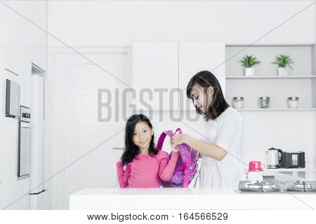 Portrait of young mother preparing her little girl for school while standing in the kitchen