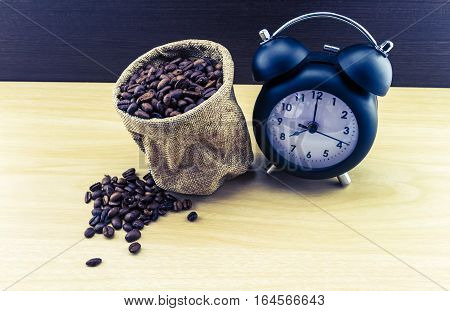 vintage classic alarm clock and coffee beans in sack sisal on wooden table