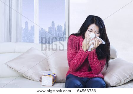 Portrait of young woman sneezing with tissue while sitting on the sofa with winter background on the window