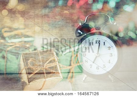 Double expose of retro alarm clock in vintage tone with gifts wooden room, creative new year background