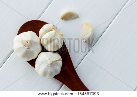 Garlic on red wooden spoon with white table background
