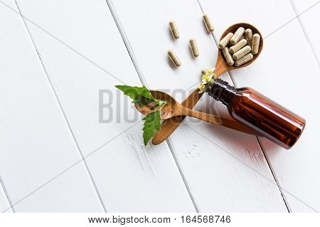 Herbal medicine in capsules from herbs on wooden spoon on table for healthy living