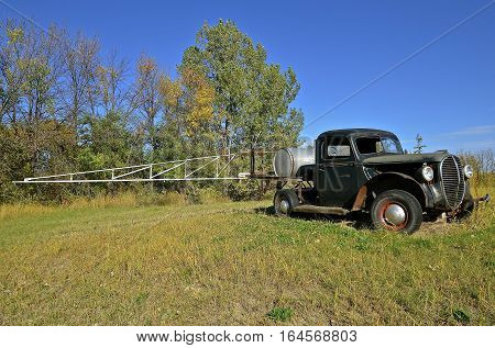 An old junker of a pickup is parked in a field with a storage tank in the box and extended boom for spraying