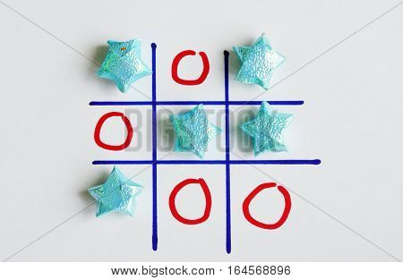 color star paper in tic-tac-toe board game on white paper