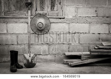 Farmer tool with boots and hat beside home with vintage tone, still life photography