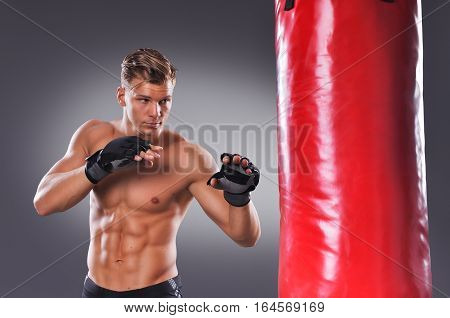 Muscular Fighter Prepare For Practicing Some Kicks With Punching Bag. Boxing On Gray Background. The