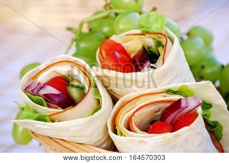 Ham and cheese wrap sandwiches in picnic basket