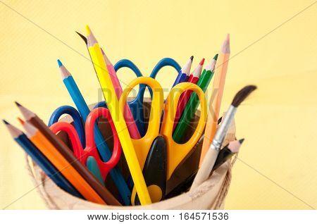 Multi-colored Pencils And Scissors On A Yellow Background Разноцветные карандаши и ножницы на желтом