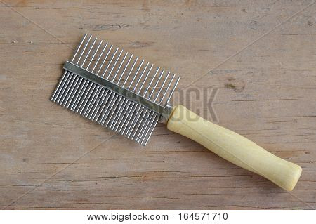 comb with teeth away and fine side for dog and cat on wooden board