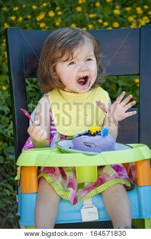 Girl with surprised look as she is shouting and singing at her birthday party/Girl singing with a surprised look on her face