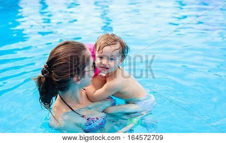 Young mother with her little daughter in the pool learning to swim