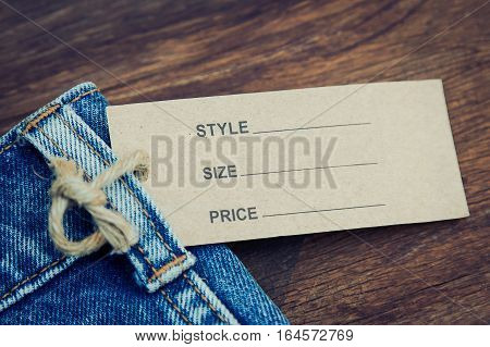 Price tag hanging on denim jean with rustic wooden style background in vintage tone