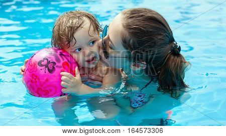 Young Mother With Her Little Daughter In The Pool