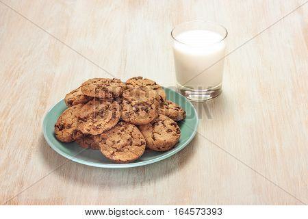 A photo of chocolate chips cookies on a plate with a glass of milk, shot on a light wooden background texture, with copyspace