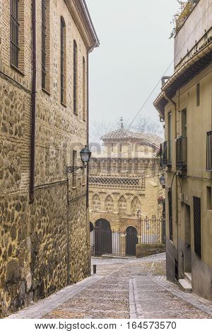 A photo of a narrow street in Toledo, Spain, in foggy weather
