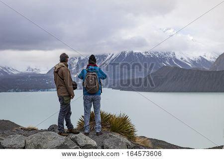 MT.COOK NATIONAL PARK NEW ZEALAND - august 31: two of tourist man standing and looking to mt.johnson foggy day in aoraki-mt.cook national park new zealand on august31 2015