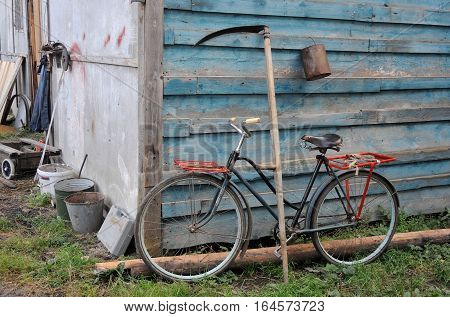 Old bicycle, scythe and economic utensils near an old barn in a poor Russian village life