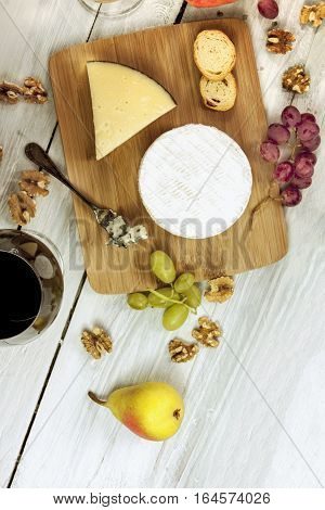 An overhead photo of a round of Camembert cheese, with a glass of red wine, bread, nuts, grapes, and other types of cheese, on a wooden board with copyspace