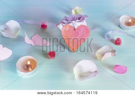 A Valentine day card with a rose flower, a paper butterfly, sweets, candles, and a little cutout heart, slightly toned