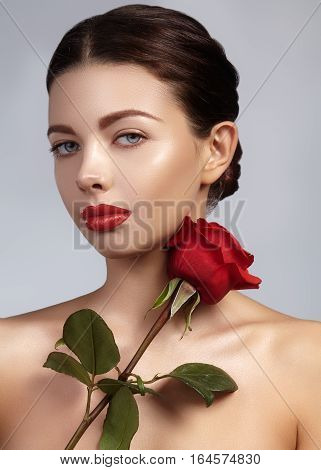 Close-up beautiful young woman with bright lipgloss makeup. Perfect clean skin sexy red lip make-up. Beautiful valentine visage with red rose flower. Romantic and sexy look for Valentines day.