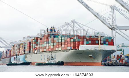 Oakland CA - January 02 2017: Tugboats PACIFIC STAR and LYNN MARIE assist COSCO JAPAN to maneuver sideways to the dock at the Port of Oakland.