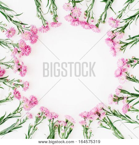 Wreath frame made of pink wildflowers green leaves branches on white background. Flat lay top view. Valentine's background