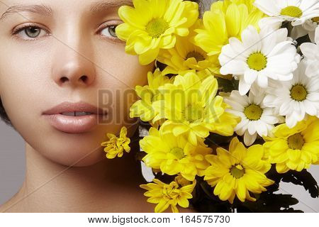 Beautiful young woman with perfect clean shiny skin natural fashion makeup with spring flowers. Close-up woman fresh spa look.