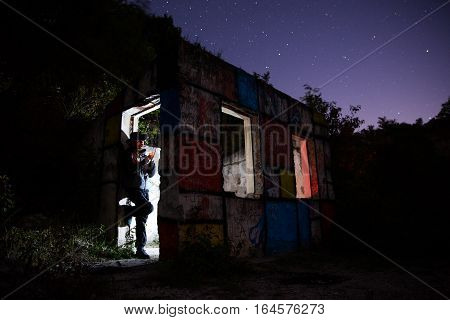 Man lights a cigarette joint in abandoned mountain house at night