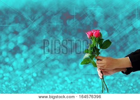 woman hands holding red rose flower on blue lights festive blurry and bokeh twinkled bright background.
