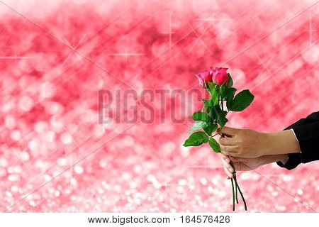 woman hands holding red rose flower on red lights festive blurry and bokeh twinkled bright background.