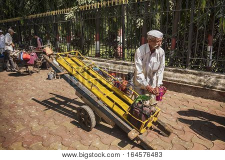 MUMBAI, INDIA - NOVEMBER 10, 2016: In Mumbai, a well-known logistics system delivers lunches through the streets. A dabawalah, or lunchbox delivery worker, located on the sidewalk just outside Mumbai's railway station starts to fill his handcart.