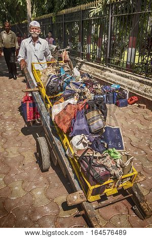 MUMBAI, INDIA - NOVEMBER 10, 2016: In Mumbai, a well-known logistics system delivers lunches through the streets. A dabbawala or lunchbox delivery worker located just outside the Mumbai train station has a full handcart of lunches ready to deliver.