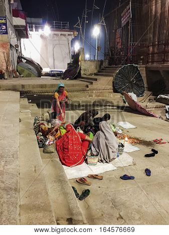 VARANASI, INDIA - NOVEMBER 15, 2016: On the morning after the Dev Diwali festival, several women sit on a blanket on one of the steps near the Ganges River during the early morning hours waiting for charitable donations.