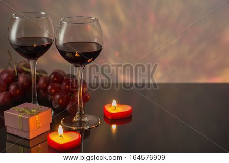 Valentines Day with a glass of red wine grapes gift candles.