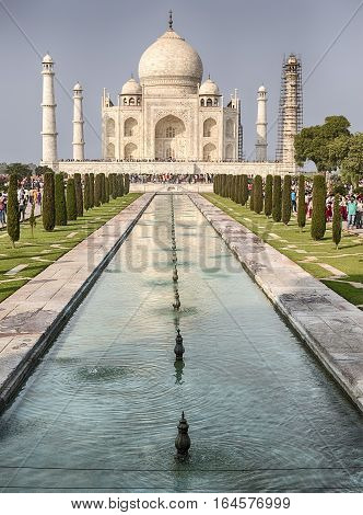 The main facade of the Taj Mahal in Agra India is located at the end of a long reflecting pool. The memorial including the four minarets at the corners is the classic example of the Mughal architecture.