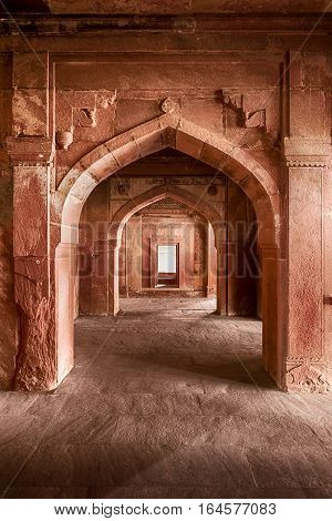 FATEHPUR, INDIA - NOVEMBER 19, 2016: A stone arch of red sandstone leads out of the Emperor's bed chamber to an outdoor courtyard in the ancient Mughal city of Fatehpur, India.