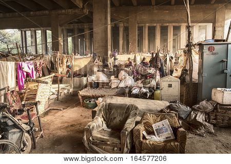 DELHI, INDIA - NOVEMBER, 20 2016: A small group of people live in slum-style housing with living quarters separated by blankets. The community is located under an elevated highway in Delhi, India.