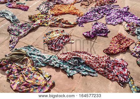 A pile of colorful hijabs or head coverings for use by tourists are scattered on the ground by the entrance of the Jama Masjid mosque in Delhi India.