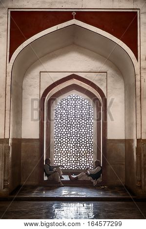 DELHI, INDIA - NOVEMBER 20, 2016: Two men frame a window inside Humayan's Tomb in Delhi, India which is richly decorated with inlaid stone. The building is a UNESCO World Heritage site.