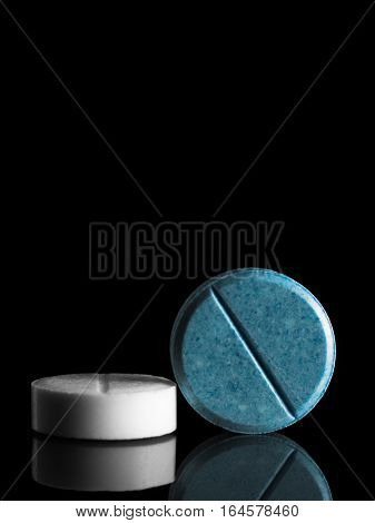 two pills (white and blue) on the mirror surface