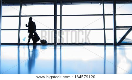 Travellers - aircraft commander with coffee to go going in airport in front of window, silhouette, wide angle