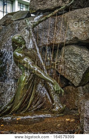 Norway Bergen . The foot of the monument - fountain to famous Norwegian composer and violinist Ole Bull . Bronze sculpture Scald playing the mythical harp. poster