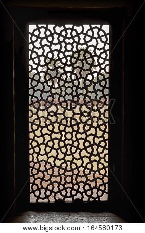DELHI, INDIA - NOVEMBER 19, 2016: A intricate carved window screen made from red sandstone inside Humayan's Tomb looks out into a courtyard with two palm trees.