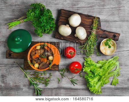 Stew meat in Burgundy in green ceramic pot with carrots onions. Spices for meat Burgundy thyme cherry tomatoes mushrooms champignons. Light white wooden background. Top view flat lay