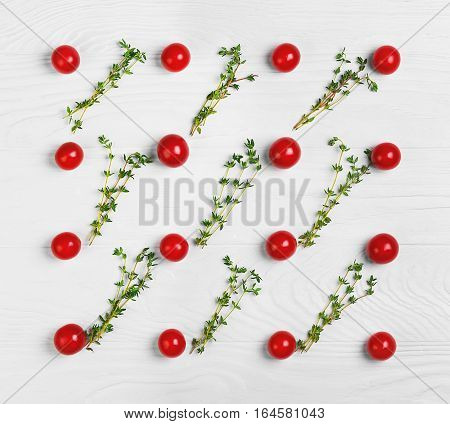 On white wooden background texture of the cherry tomatoes. Between cherry tomatoes thyme. Cooking concept texture background. Top view flat lay.