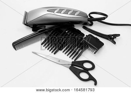 electric hair clipper, comb and clamp on a white background
