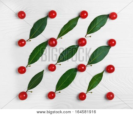 On white wooden background texture of the cherry tomatoes. Between cherry tomatoes laurel leaves. Cooking concept texture background. Top view flat lay.