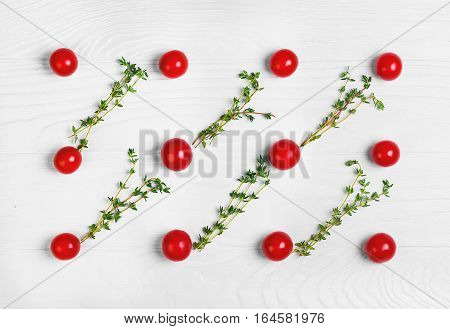 On white wooden background pattern texture of the cherry tomatoes. Between cherry tomatoes thyme. Cooking concept texture background. Top view flat lay.