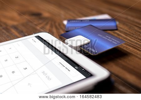 Credit card payment on a swipe or chip reader app on a tablet used by small or online businesses. The electronic device is used as a modern cash register or for banking.