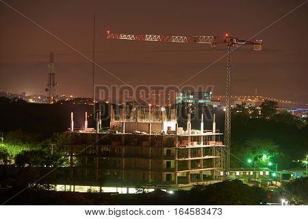 Building crane at night with building under construction